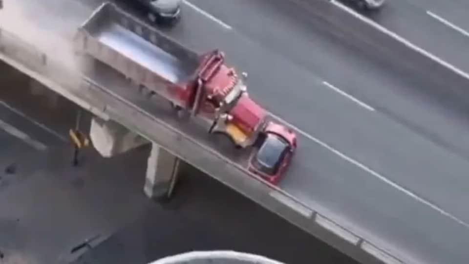Une image aérienne d'une autoroute où un camion pousse une petite voiture rouge.