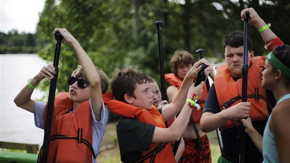 Des enfants dans un camp de vacances d'activités nautiques apprennent comment tenir leur pagaie, sous les conseils d'une monitrice.