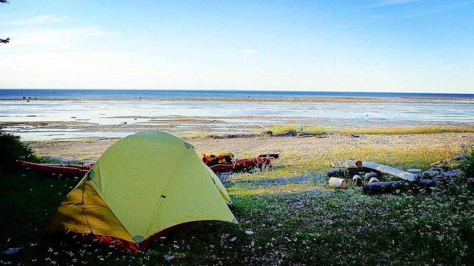 Camping sauvage sur l'île d'Anticosti : on aperçoit une tente, un kayak et des bûches, sur le bord de l'eau.