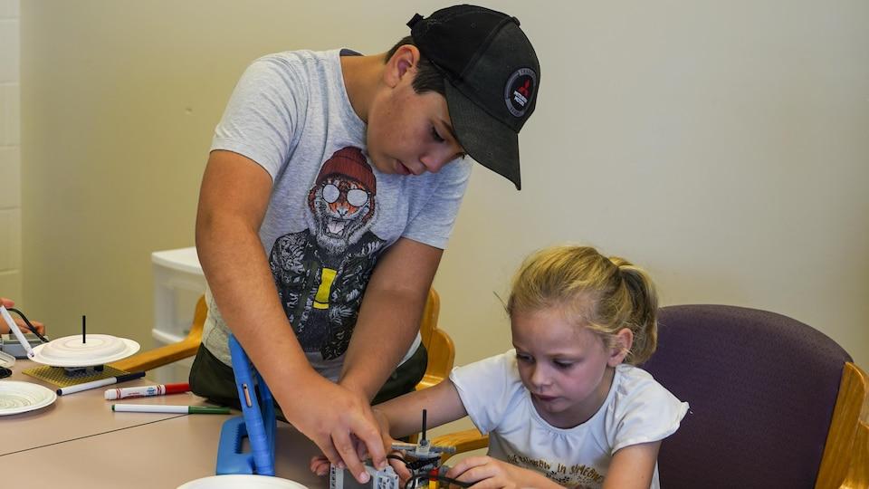 Deux enfants en train d'assembler des pièces de lego.