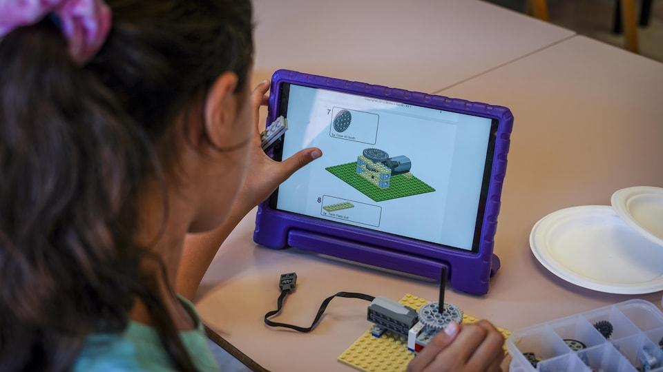 Une jeune fille regarde des instructions sur une tablette.
