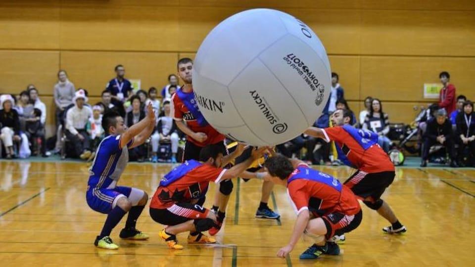 Des joueurs et un immense ballon dans un gymnase