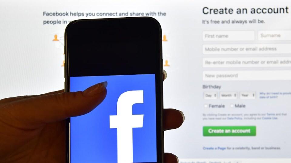 Une main tient un téléphone intelligent montrant le logo de Facebook devant l'écran d'un ordinateur qui affiche la page d'accueil de Facebook.