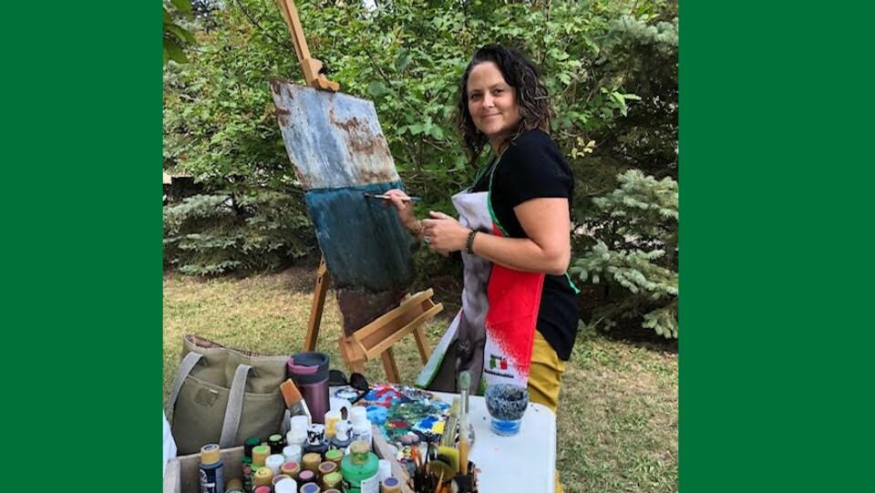 Peintre de sexe féminin au regard perçant et sourire de Joconde avec son chevalet et ses tubes de peinture dans un sous-bois ou il fait bon vivre.