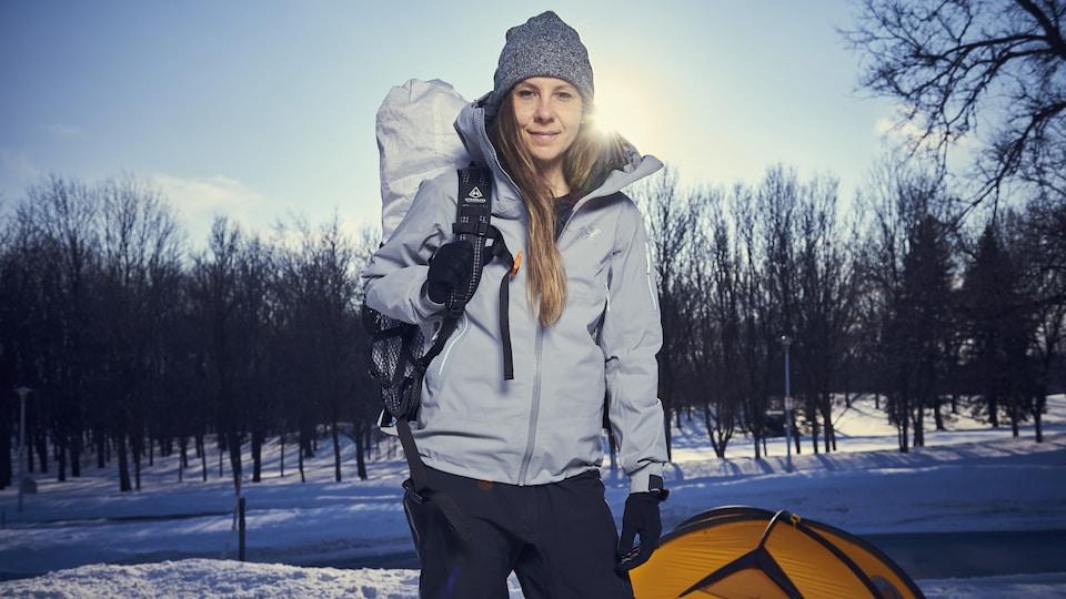 Caroline Côté pose devant sa tente, sac au dos, dans un parc.