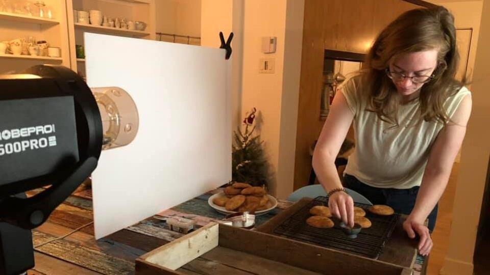 La photographe Catherine Côté, dans son atelier, s'affairant à composer une mise en place culinaire.