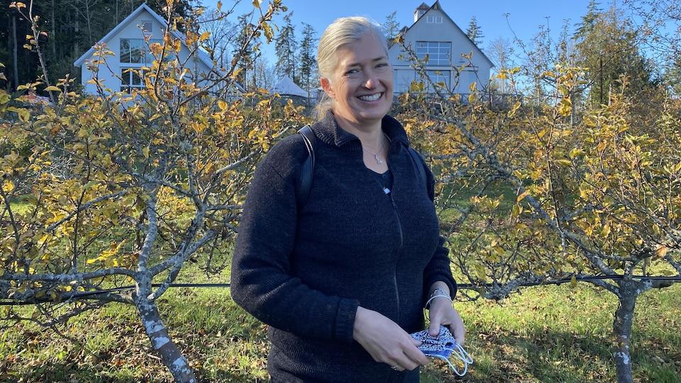 Une femme souriante dans un champ de pommier