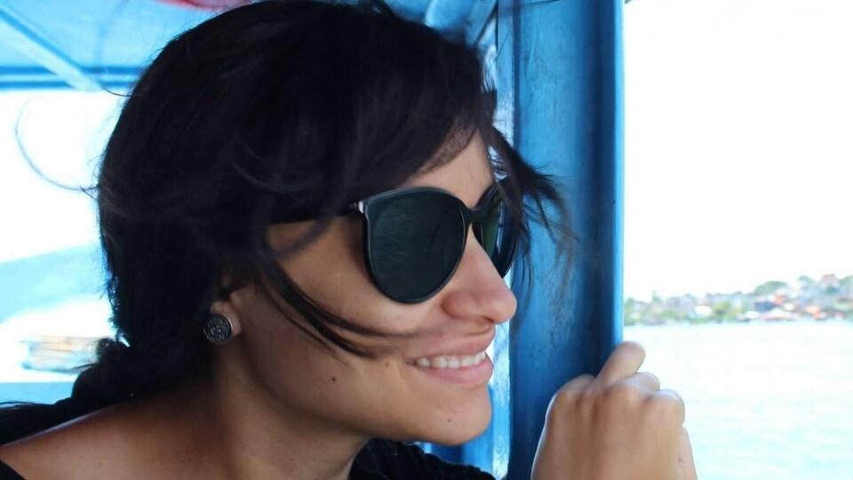 Une dame portant des lunettes de soleil, à bord d'un bateau.