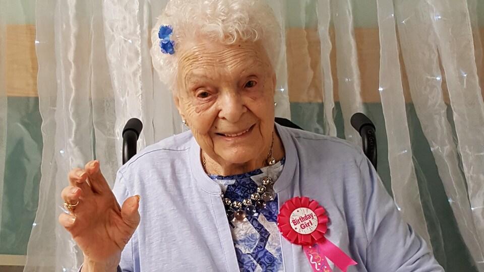 Gilberte Gervais assise dans un fauteuil roulant lors de la célébration de son 100e anniversaire.