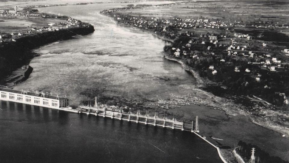 Photo en noir et blanc d'une vue aérienne d'une centrale hydroélectrique sur une rivière.