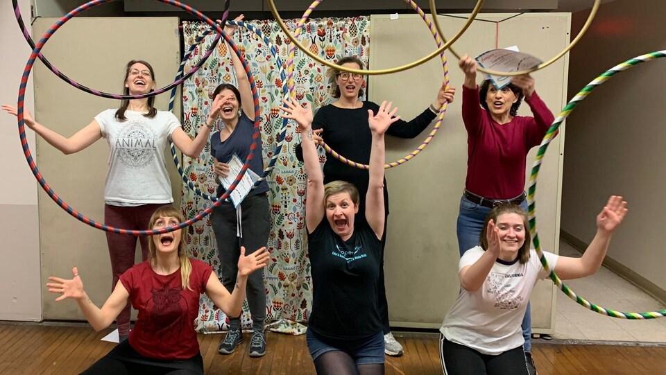 Sept élèves enthousiates d'un cours de cerceau jettent leur cerceau en l'air après leur entraînement