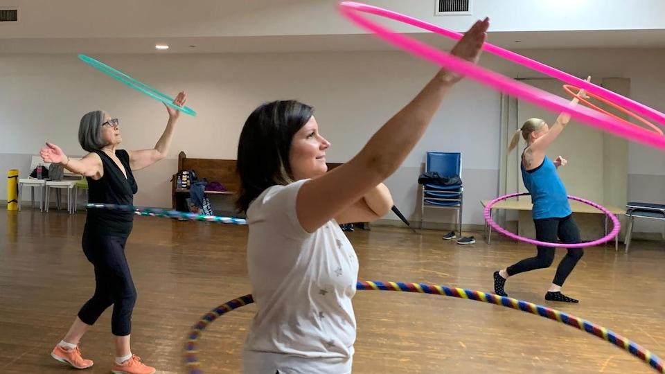 Caroline Vanderghem s'entraîne au hula-hoop, un cerceau autour de la taille et un autre autour du bras.