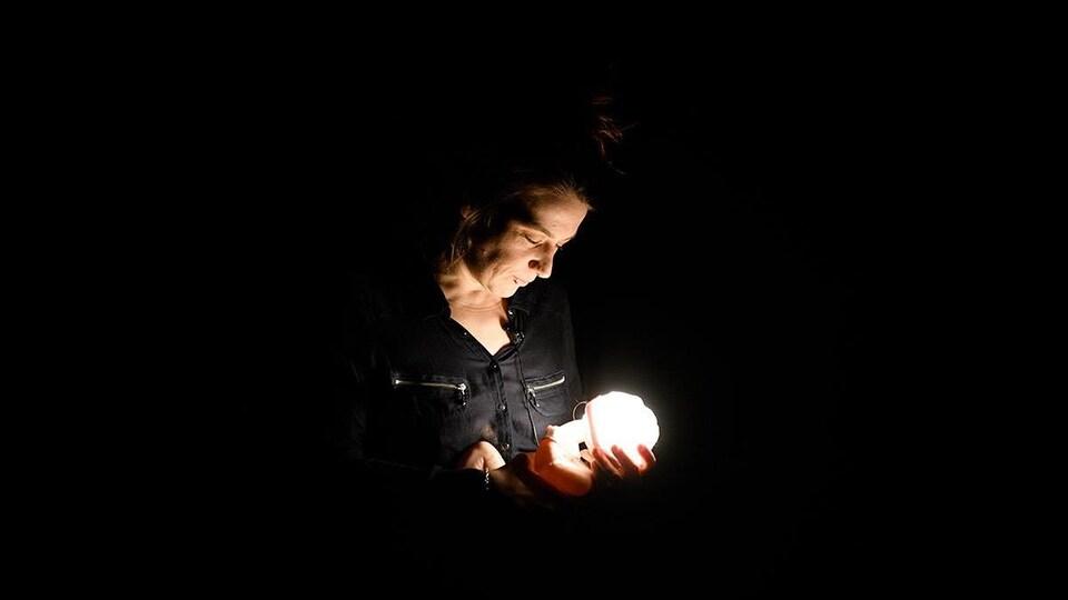 Une femme tient une poupée qui s'illumine.