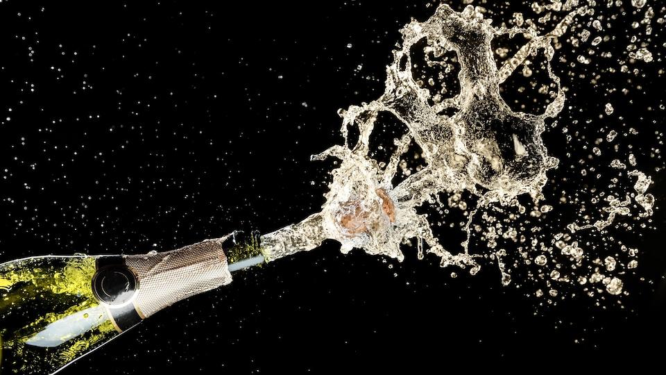 Une bouteille ouverte dont le liquide explose à sa sortie.