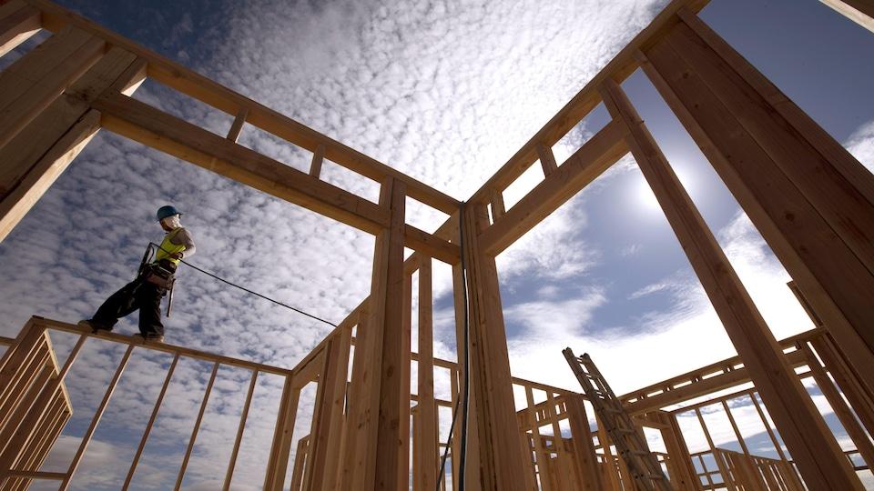 Un travailleur debout sur la structure d'une maison en construction.