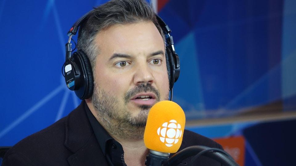 Charles Lafortune derrière un micro dans un studio radio de Radio-Canada.