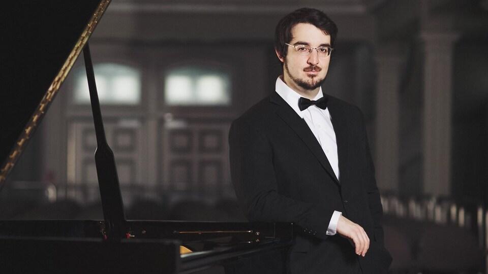 Le pianiste Charles Richard-Hamelin avec un noeud papillon, debout à côté d'un piano.