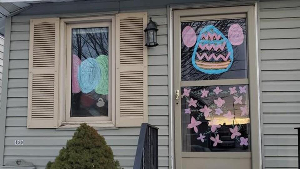 Des peintures d'enfants montrant des œufs de Pâques décorent une maison.