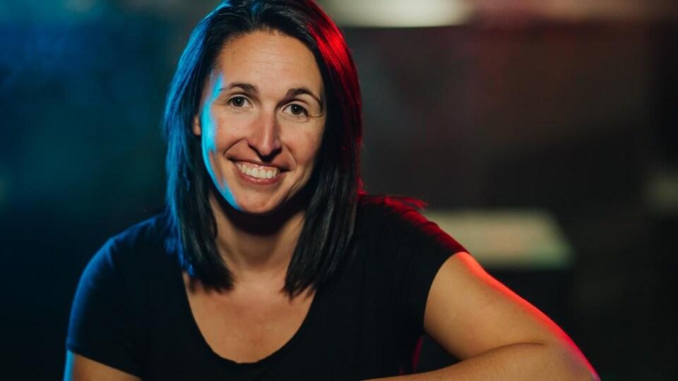 Une jeune femme pose devant la caméra assise sur un tabouret à l'intérieur d'un bar.