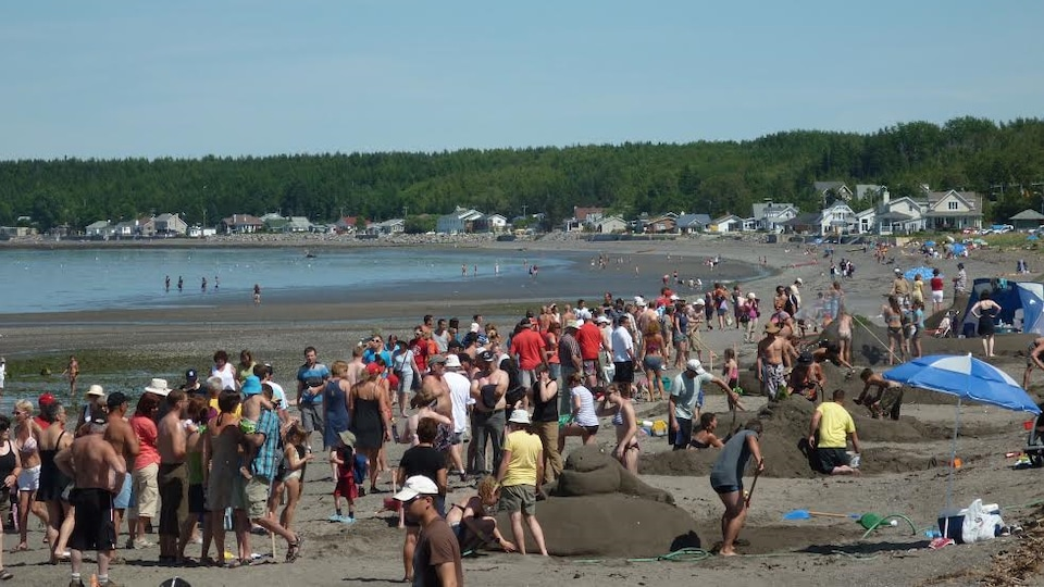 Des passants et des participants sur la plage lors du concours de châteaux de sable de Sainte-Luce à l'été 2017.