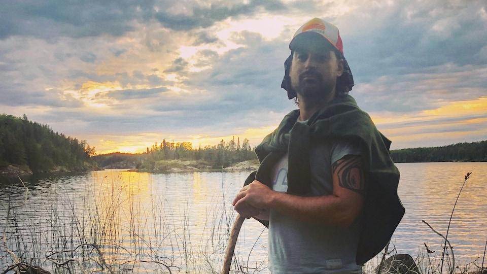 Chris Gaudry, réalisateur métis, musicien et passionné de nature est debout sur les rives d'un étendu d'eau.