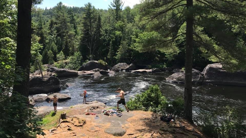 Trois personnes en maillot de bain sur la rive d'un cours d'eau.