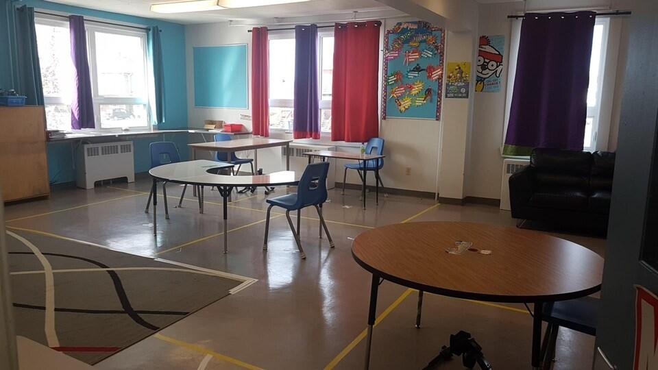 Une classe du primaire avec des tables et des chaises distanciés de 2 mètres.