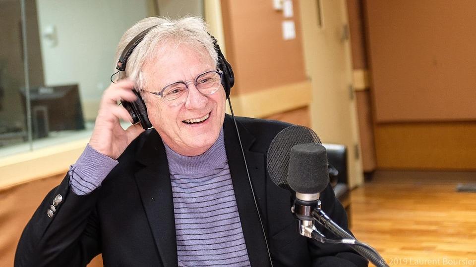 Claude Saucier, des écouteurs sur la tête, sourit devant un micro dans un studio de radio.