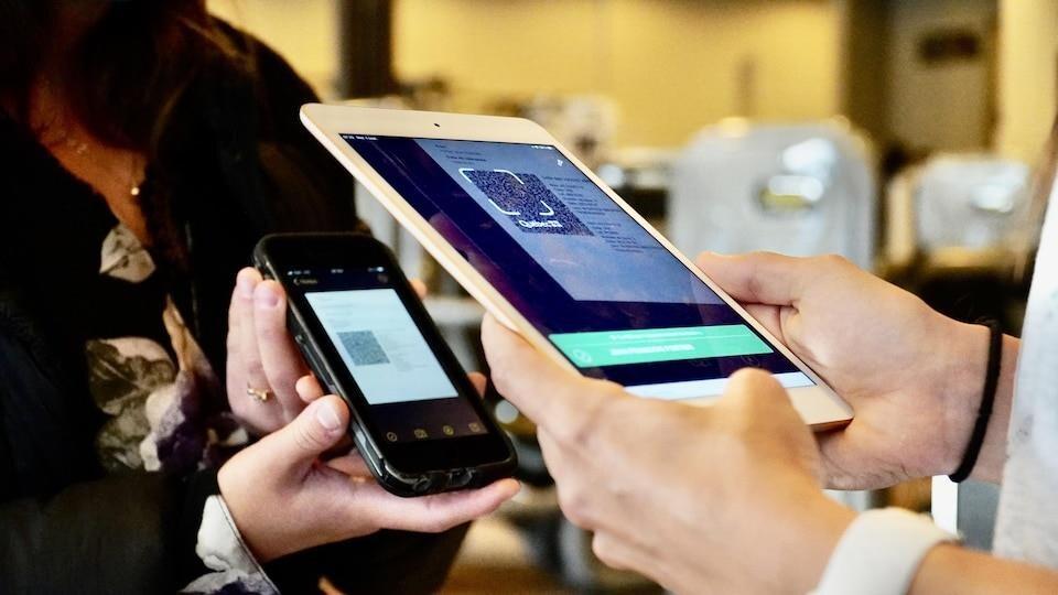 Une employée tient une tablette électronique pour lire un code QR sur le téléphone d'une cliente.