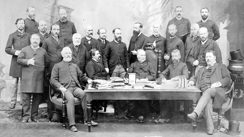Les dirigeants de cinq provinces du Canada se rencontrent à Québec en 1887. Ils posent en veston devant une table où se trouvent des piles de livres.