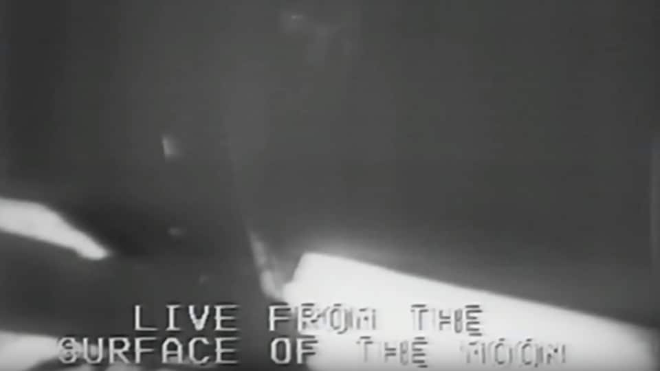 Image en direct de Neil Armstrong sur le point de fouler le sol lunaire le 20 juillet 1969. Les mots anglais en direct de la surface la Lune apparaissent en bas de l'image.