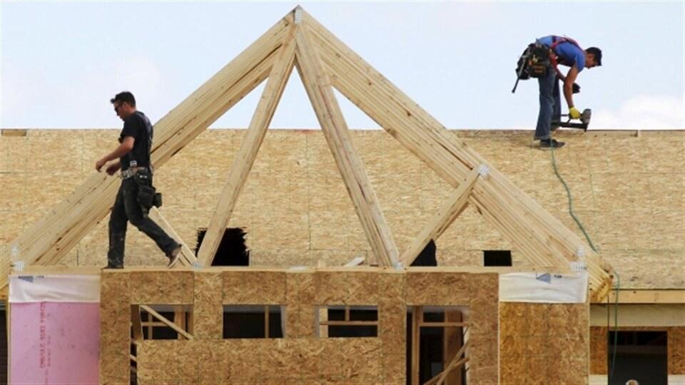 Des travailleurs de la construction bâtissent une maison à Calgary en 2015.