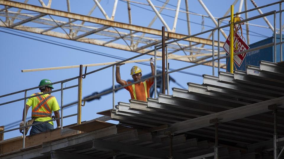Des ouvriers sur un édifice en construction, avec une grue en arrière-plan.