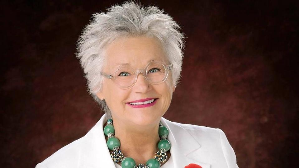 Une femme portant un veston blanc sourit à la caméra.