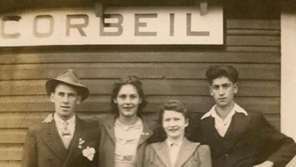Les quatre individus debout devant la gare.