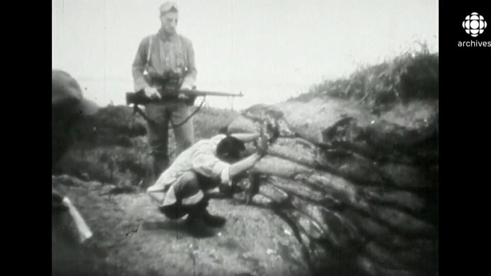 Un soldat avec un fusil surveille un prisonnier accroupi dans une tranchée.