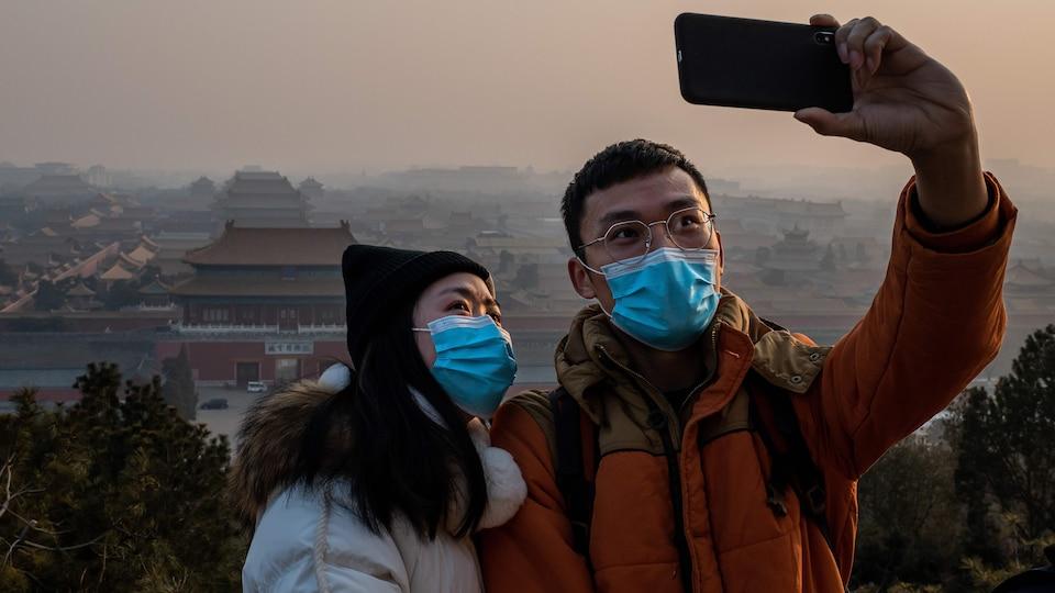 Le jeune homme prend un autoportrait du couple, qui porte des masques, avec la Cité interdite en arrière-plan.