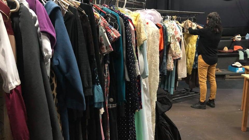 Une femme dans un entrepôt de costumes de théâtre