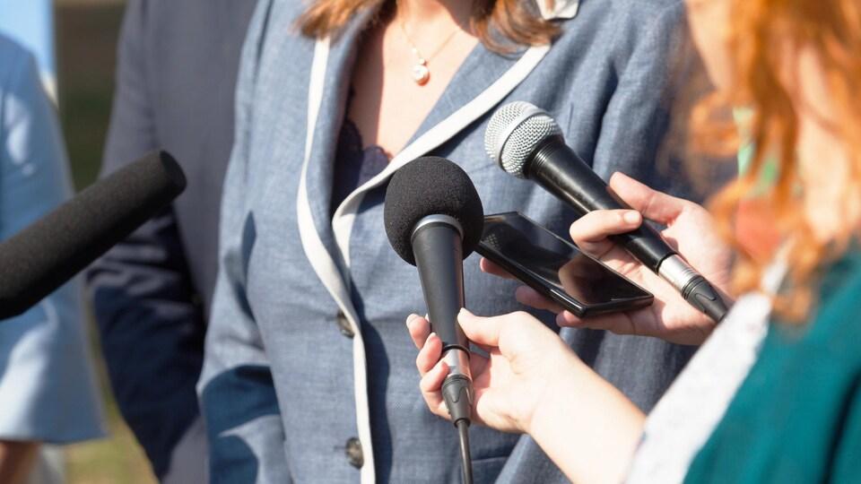 Une politicienne répond aux questions des journalistes.