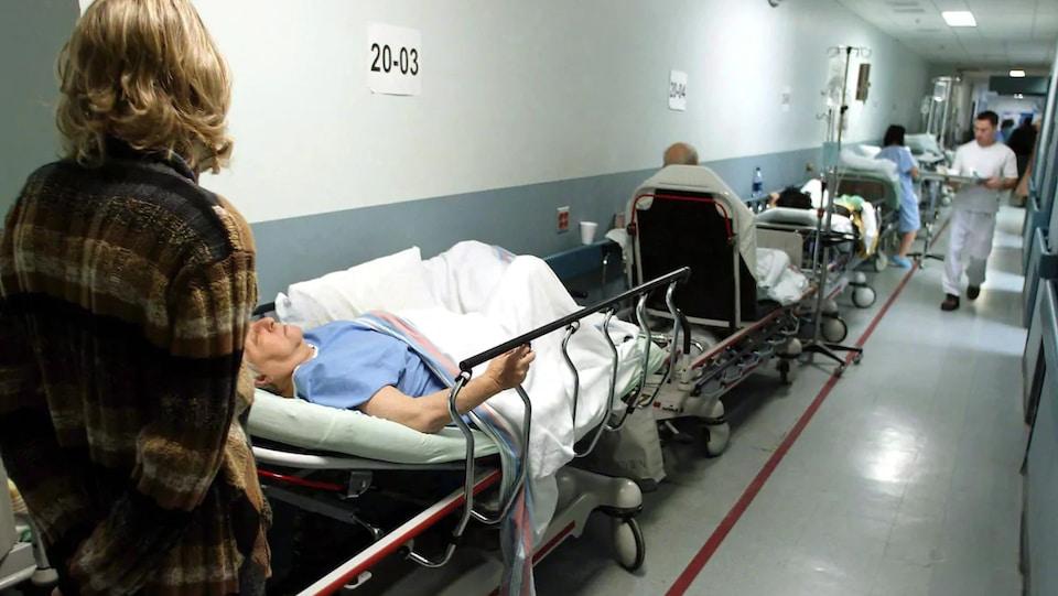 Des patients sur des lits d'hôpitaux dans un couloir.