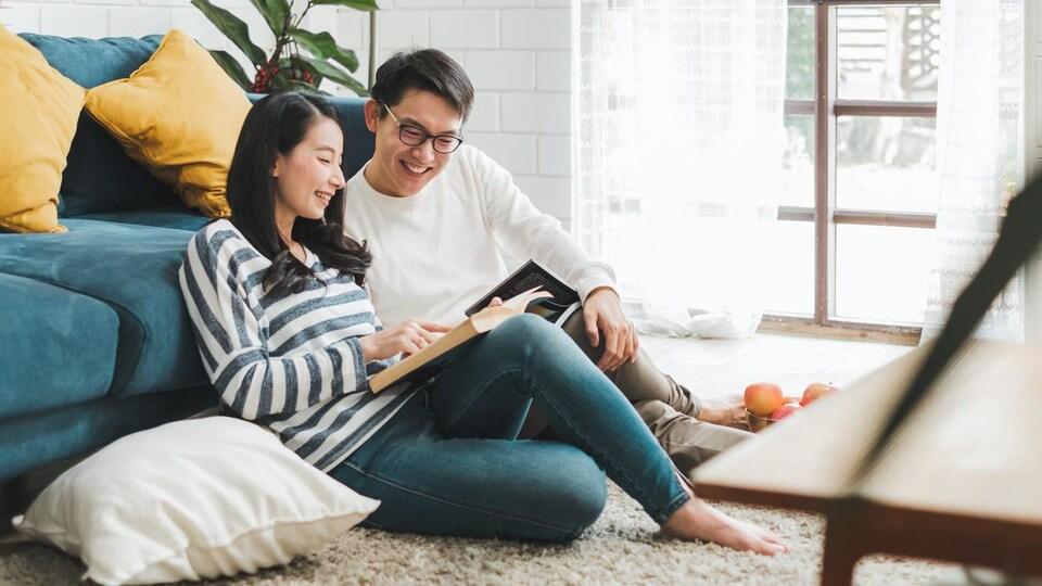Un couple assis par terre dans un salon en train de regarder le même livre.