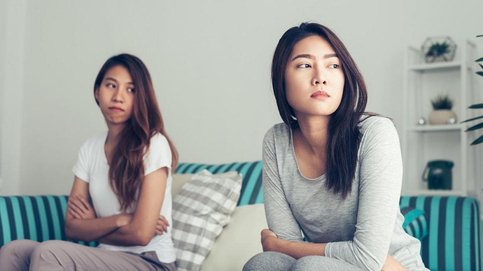 Un couple de femmes regardant au loin d'un air triste en tenant leurs bras croisés.