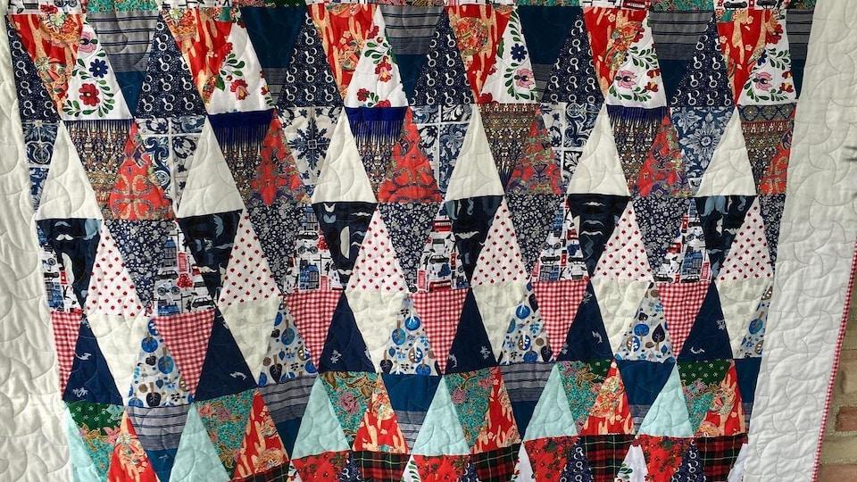 Une courtepointe conçue de triangles de tissus retrouvés autour du monde.