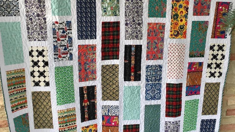 Une courtepointe conçue de rectangles de tissus retrouvés autour du monde.