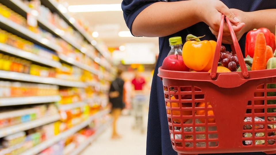 Une dame tient un panier de fruits et de légumes dans une épicerie.
