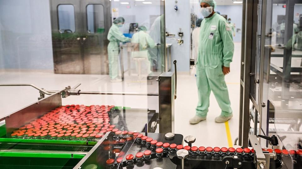 Un technicien de laboratoire habillé d'une combinaison et portant un masque observe une machine de loin.