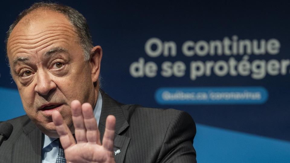 Christian Dubé en conférence de presse, esquisse un geste de la main en répondant à une question.