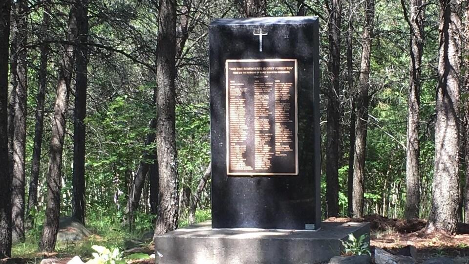 Une grande pierre porte une croix et une plaque avec une grande liste de noms des personnes enterrés sur l'ancien site funéraire de Coniston.