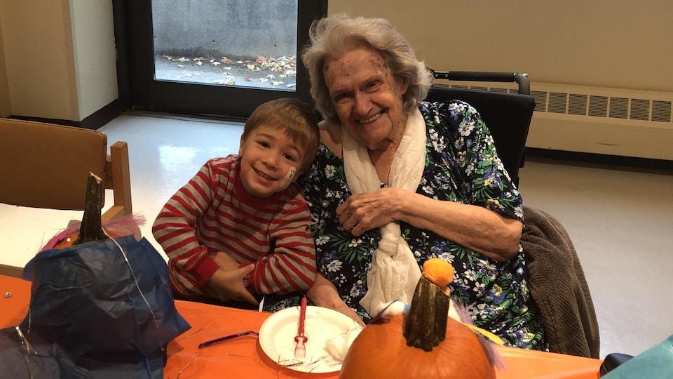 Un petit garçon souriant en compagnie d'une dame âgée.