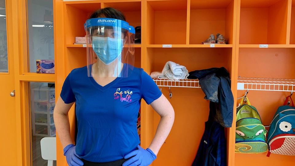 Une éducatrice avec des gants, un masque et une visière pose devant des casiers.